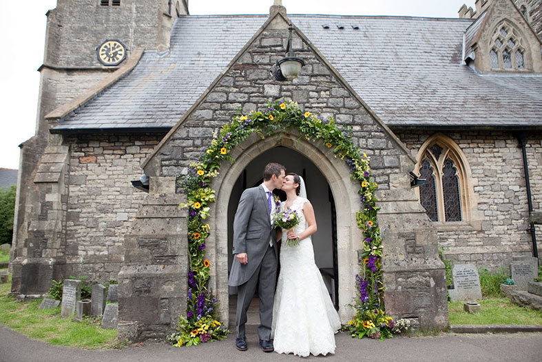 Floral arch at the church entrance by Organic Blooms