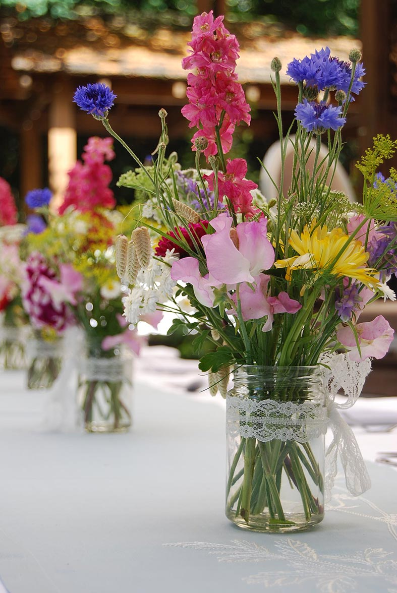 Fresh picked seasonal garden flowers in recycled jars